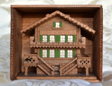 A wooden swiss cottage in a box