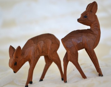 two carved wooden deer